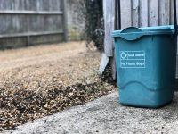 green bin sitting on sidewalk outside house