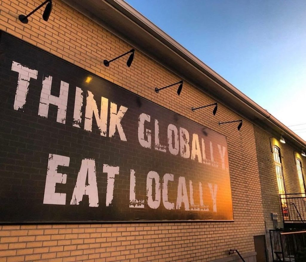 Borealis building exterior with text Think globally eat locally on the side